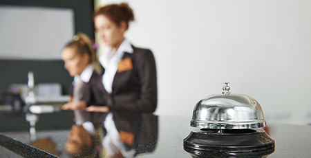front desk agents at hotel with bell